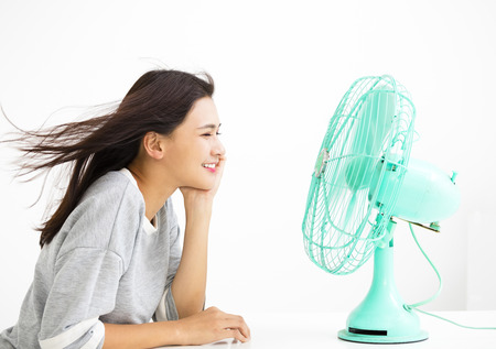 home: smiling woman cooling herself by electric fan Stock Photo