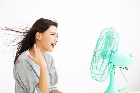 Lächelnde Frau kühlt sich durch elektrischen Ventilator
