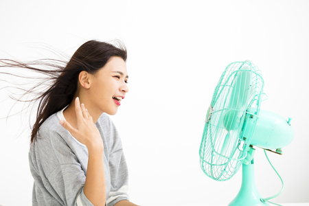 smiling woman cooling herself by electric fan  Stock Photo