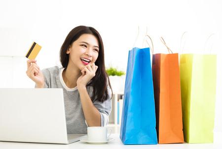 신용 카드를 제시하고 온라인으로 쇼핑하는 젊은 여성