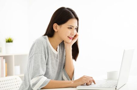home: beautiful young woman smiling and looking at laptop
