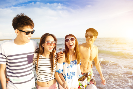 happy young group walking on the beach at summer vacation Stock Photo