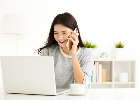 home: young Woman working on laptop and talking on the phone