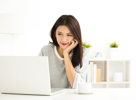 contact: young Woman working on laptop in living room Stock Photo