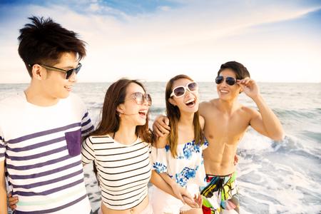 ビーチの上を歩く幸せな若いグループが夏の休暇を楽しむ 写真素材
