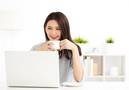 Jonge vrouw werken op laptop in de woonkamer