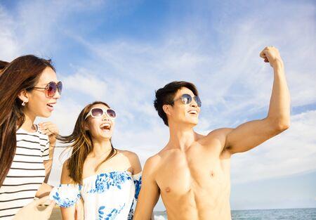 voyage: Jeune homme montrant ses amis ses gros muscles sur la plage