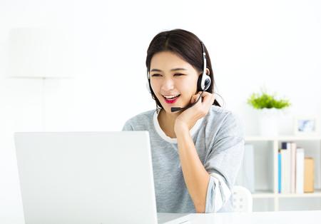 젊은 여자 헤드셋 및 노트북 비디오 호출에서 이야기 라인
