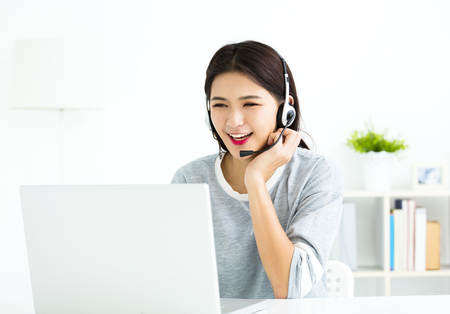 young woman  talking in  video call on line with headsets and  laptop