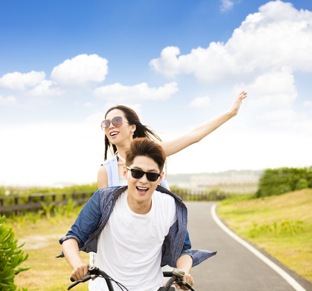 happy young couple riding bicycle  in the park