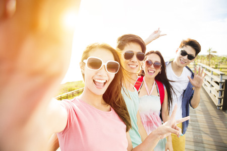 幸せな若いグループのお友達が夏休みに selfie を引き継ぐ