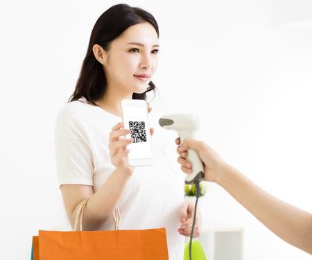 Giovane donna paga con smart phone con codice qr Archivio Fotografico - 79215477