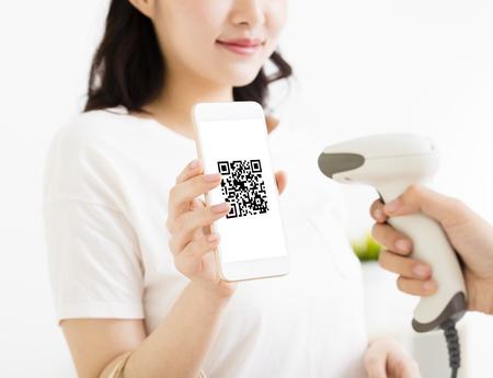 Jonge vrouw betalen met slimme telefoon met qr code Stockfoto