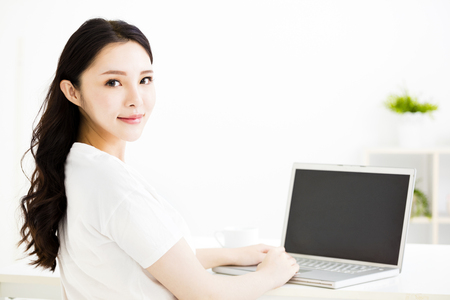living room interior: beautiful young smiling woman  with laptop