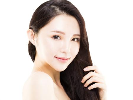 彼女の長く、健康な髪に触れる若い女性