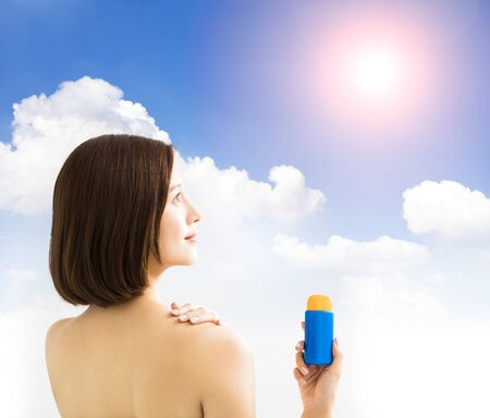 healthy body: young woman showing sun protection lotion