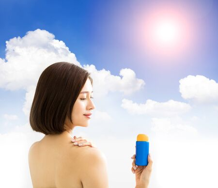 young woman showing sun protection lotion