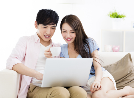 Happy young couple sitting on sofa  with laptop Stock Photo - 80506430