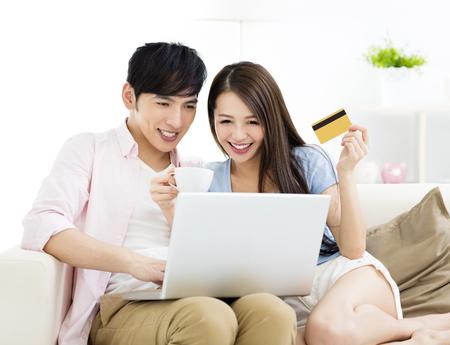 ノート パソコンをソファーの上に座って幸せな若いカップル