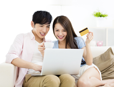Happy young couple sitting on sofa  with laptop