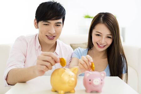 Young happy couple putting coin into piggy bank