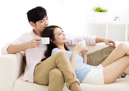 Portrait der lächelnden jungen Paar sitzt auf Sofa Standard-Bild - 80634988