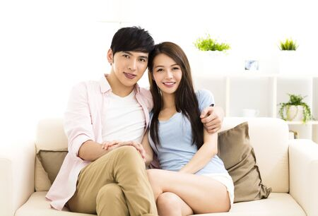 affections: Portrait of  smiling  young couple sitting on sofa
