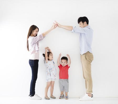 Gelukkige familie die het huisteken maakt vóór witte muur Stockfoto - 80701705