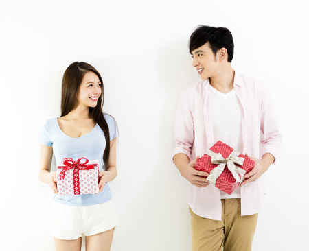 happy young couple showing the gift box