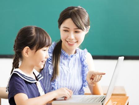Joven profesor ayudar a niño con la lección de computadora Foto de archivo