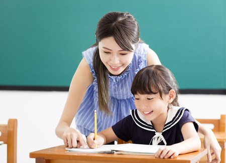 young Teacher helping child with writing lesson Фото со стока - 81268123