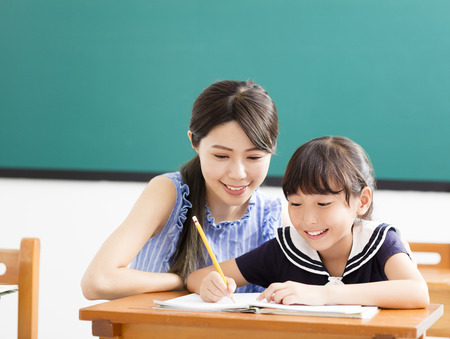 young Teacher helping child with writing lesson  Stock Photo
