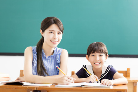 Giovane insegnante che aiuta bambino con la lezione di scrittura Archivio Fotografico - 81360870