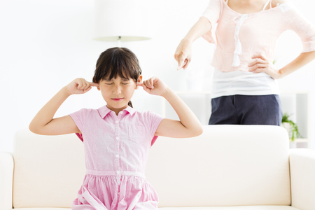 Upset little girl covering her ears while her mother angry