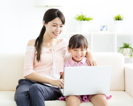 mother with  daughter looking at Laptop  on sofa