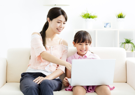 mother with  daughter looking at Laptop  on sofa Banco de Imagens