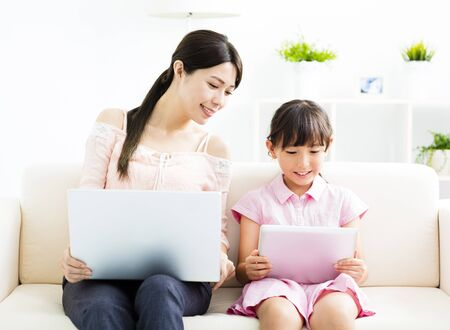 mother with  daughter looking at Laptop� on sofa photo