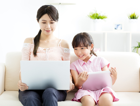 mother with  daughter looking at Laptop on sofa photo