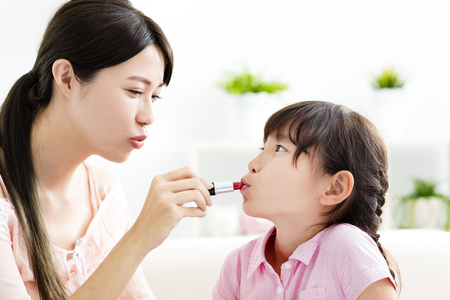 face to face: happy Mother and little girl  doing your makeup   Stock Photo