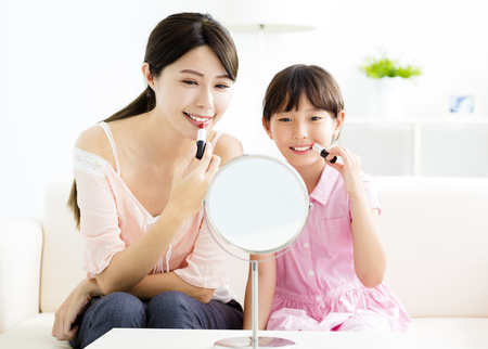 happy Mother and little girl  doing your makeup photo