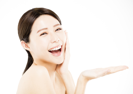 empty: happy Beauty woman showing  beauty product on her hand Stock Photo