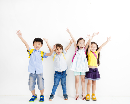 Group of happy smiling kids raise hands Archivio Fotografico
