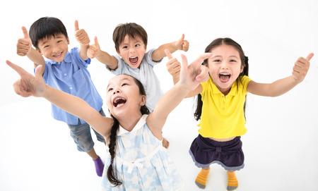Groep gelukkige lachende kinderen met duim omhoog
