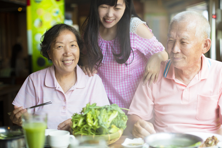 Senior Couple and daughter Enjoying hot pots In Restaurant photo