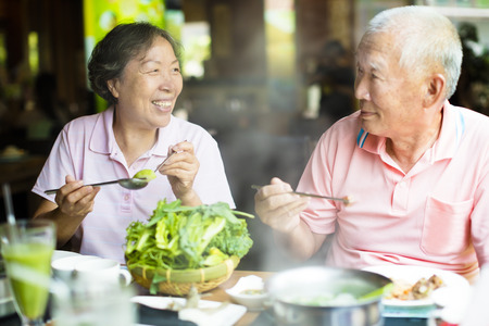 Feliz Senior Pareja Disfrutar de ollas calientes en el restaurante