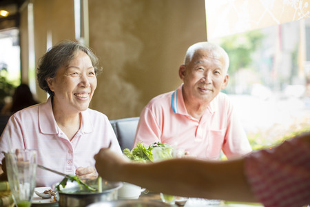 Senior Couple and family eating hot pots In Restaurant photo