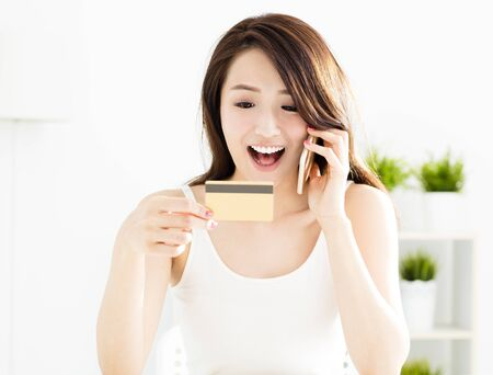 technology: woman buying online with  credit card and smart phone