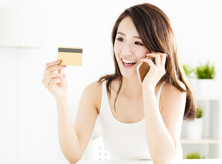 technology transaction: woman buying online with  credit card and smart phone