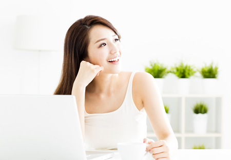 smiling young  woman with laptop in living room