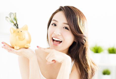 happy young woman showing piggy bank with money